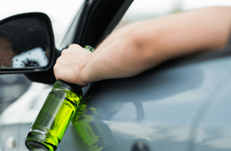 Man driving car while holding a liquor bottle out of his vehicle window