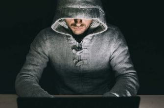 Man in a hooded sweatshirt sitting in front of a laptop computer in a dark room