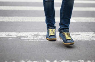 Feet of pedestrian walking in a crosswalk