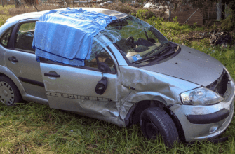 Wrecked mini-van with sheet covering the window after a fatal accident